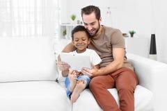 Padre feliz con el muchacho afroamericano adoptado Foto de archivo