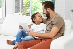 Padre feliz con el muchacho afroamericano adoptado Imagenes de archivo