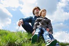 Padre feliz con el pequeño hijo que se sienta en hierba verde y la mirada imagen de archivo