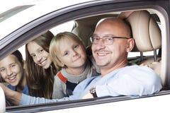 Padre feliz con los niños en el coche Fotografía de archivo
