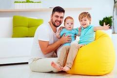 Padre feliz con los seis de los años hijos de seis meses y, en casa Imágenes de archivo libres de regalías