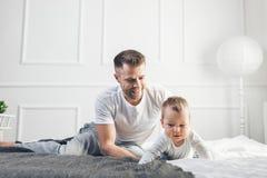Padre feliz con su hijo que juega en casa en la cama fotos de archivo