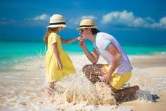 Padre feliz con su pequeña hija que disfruta de vacaciones de la playa imagenes de archivo