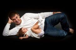Padre feliz con su pequeña mentira de la hija Imagen de archivo