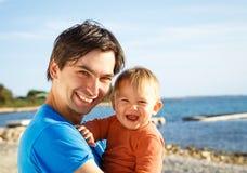 Padre feliz con su pequeño hijo en el mar imágenes de archivo libres de regalías