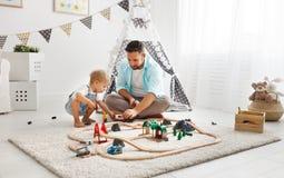 Padre feliz de la familia e hijo del niño que juega en ferrocarril del juguete en el pl imagenes de archivo