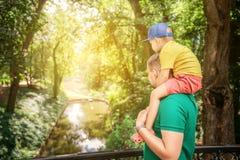 Padre feliz de la familia e hijo del niño que juega y que ríe en la naturaleza de la puesta del sol Foto de archivo libre de regalías