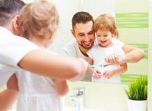 Padre feliz de la familia y muchacha del niño que cepilla sus dientes en bathroo Imagen de archivo