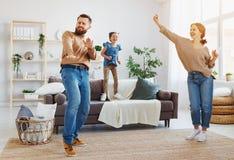 Padre feliz de la madre de la familia e hija del ni?o que baila en casa fotografía de archivo libre de regalías