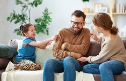Padre feliz de la madre de la familia e hija del ni?o que se r?e del hogar fotografía de archivo libre de regalías