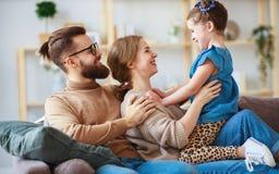 Padre feliz de la madre de la familia e hija del ni?o que se r?e del hogar fotos de archivo