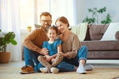 Padre feliz de la madre de la familia e hija del ni?o que se r?e del hogar imagen de archivo libre de regalías
