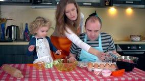 Padre feliz de la madre de la familia e hija linda que hacen la galleta junto en cocina metrajes