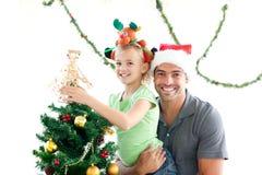 Padre feliz e hija que adornan el árbol Fotos de archivo libres de regalías