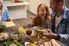 Padre feliz e hija que comen junto foto de archivo