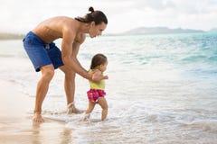 Padre feliz e hija que juegan junto en la playa afuera imagen de archivo