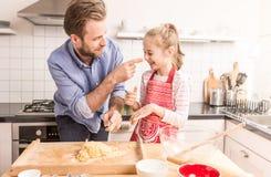 Padre feliz e hija que preparan la pasta de la galleta en la cocina Fotos de archivo libres de regalías