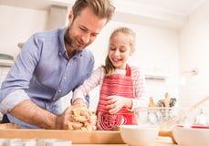 Padre feliz e hija que preparan la pasta de la galleta en la cocina Imagenes de archivo