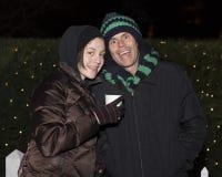 Padre feliz e hija que se colocan en el frío delante de arbustos con las luces de la Navidad Foto de archivo