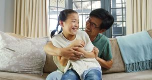Padre feliz e hija que se divierten en la sala de estar 4k almacen de video