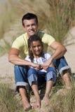 Padre feliz e hija que se sientan en la playa Imagen de archivo