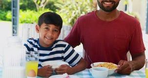 Padre feliz e hijo que desayunan 4k almacen de video