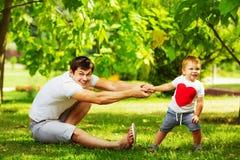 Padre feliz e hijo que juegan junto divertirse en su verde Imagenes de archivo