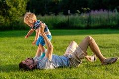 Padre feliz e hijo que se divierten al aire libre en prado Imagen de archivo libre de regalías