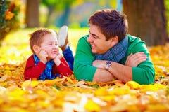 Padre feliz e hijo que se divierten en parque del otoño Foto de archivo