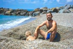 Padre feliz e hijo que se divierten que juega en la playa fotos de archivo