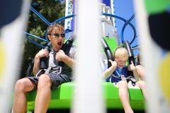 Padre feliz e hijo que se divierten que monta un paseo del carnaval en un día de verano imagenes de archivo