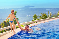 Padre feliz e hijo que se relajan en piscina del infinito en la isla tropical Imagenes de archivo