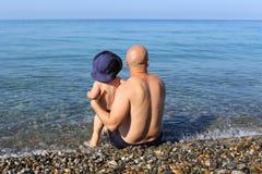 Padre feliz e hijo que se sientan en la playa Imagen de archivo libre de regalías