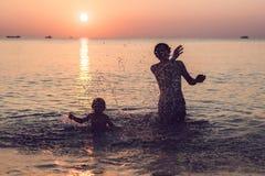 Padre feliz e hijo que tienen tiempo de la familia de la calidad en la playa encendido Imagen de archivo libre de regalías