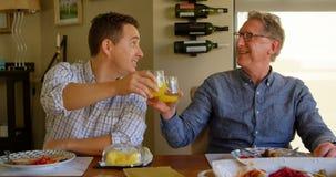 Padre feliz e hijo que tuestan los vidrios del jugo en casa 4k almacen de video