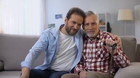 Padre feliz e hijo sonrientes que miran a la cámara, seguro social, estadísticas metrajes