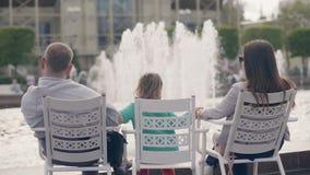 Padre feliz, hija de la madre junto que sienta la fuente delantera del verano en parque de la ciudad metrajes