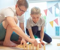 Padre feliz joven que juega con su hijo con los bloques de madera en el piso foto de archivo