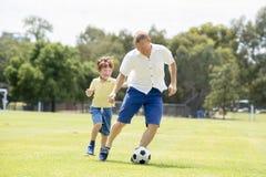 Padre feliz joven y excitado poco 7 o 8 años del hijo que juega junto al fútbol del fútbol en el jardín del parque de la ciudad q fotografía de archivo libre de regalías