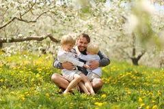 Padre feliz Playing con sus niños jovenes afuera el la primavera D foto de archivo