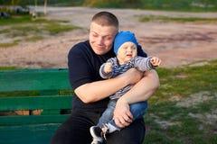 Padre feliz que abraza a su hijo enojado en un banco en el parque imágenes de archivo libres de regalías
