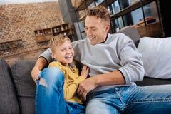 Padre feliz que cosquillea a su hijo y que ríe con él Foto de archivo