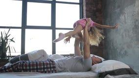 Padre feliz que deja a su hija volar en dormitorio almacen de metraje de vídeo