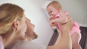 Padre feliz que detiene al bebé en las manos Bebé alegre en abrazo del padre almacen de metraje de vídeo