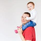Padre feliz que detiene al niño en el fondo blanco Fotografía de archivo libre de regalías