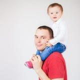 Padre feliz que detiene al niño en el fondo blanco Foto de archivo libre de regalías