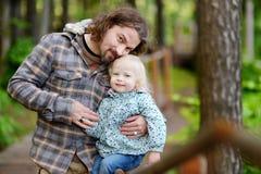Padre feliz que detiene a su pequeña hija imagen de archivo