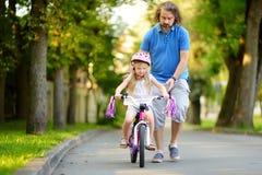 Padre feliz que enseña a su pequeña hija a montar una bicicleta Niño que aprende montar una bici Imagen de archivo libre de regalías