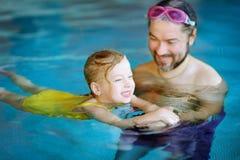 Padre feliz que enseña a su pequeña hija a nadar Niño feliz activo que aprende nadar Fotos de archivo libres de regalías