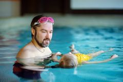 Padre feliz que enseña a su pequeña hija a nadar Niño feliz activo que aprende nadar Foto de archivo